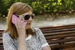Jovem mulher bonita que usa seu móbil no parque foto de stock