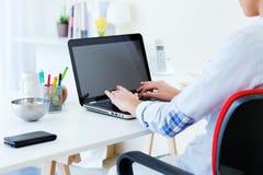 Jovem mulher bonita que usa seu portátil no escritório Imagens de Stock