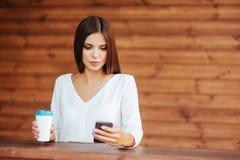 Jovem mulher bonita que usa seu smartphone e bebendo o café imagem de stock