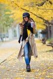 Jovem mulher bonita que usa seu telefone celular ao andar através do parque durante o outono fotografia de stock