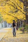 Jovem mulher bonita que usa seu telefone celular ao andar através do parque durante o outono imagem de stock