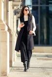Jovem mulher bonita que usa seu telefone celular ao andar na rua imagens de stock