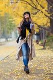 Jovem mulher bonita que usa seu telefone celular ao olhar ao céu e ao andar através do parque durante o outono fotografia de stock