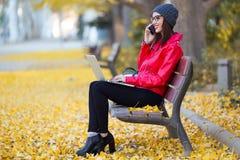 Jovem mulher bonita que usa seu telefone celular ao trabalhar com o portátil no outono Fotografia de Stock