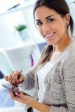 Jovem mulher bonita que usa seu telefone celular em casa Fotografia de Stock