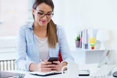 Jovem mulher bonita que usa seu telefone celular no escritório Foto de Stock Royalty Free