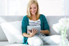 Jovem mulher bonita que usa sua tabuleta digital em casa Foto de Stock