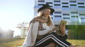 Jovem mulher bonita que usa sua tabuleta para conversar com amigos ao sentar-se na grama no parque filme