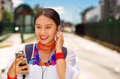Jovem mulher bonita que veste a blusa andina tradicional e a trouxa azul, ônibus de espera na plataforma da estação do ar livre Imagem de Stock