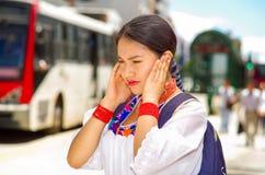 Jovem mulher bonita que veste a blusa andina tradicional e a trouxa azul, ônibus de espera na plataforma da estação do ar livre Fotografia de Stock Royalty Free