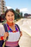 Jovem mulher bonita que veste a blusa andina tradicional e a trouxa azul, ônibus de espera na plataforma da estação do ar livre Fotos de Stock