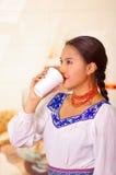 Jovem mulher bonita que veste a blusa andina tradicional, estando o café acima bebendo da caneca branca Imagem de Stock Royalty Free