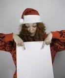 Jovem mulher bonita que veste o chapéu de Santa e que guarda o sinal vazio Imagens de Stock Royalty Free