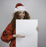 Jovem mulher bonita que veste o chapéu de Santa e que guarda o sinal vazio Fotos de Stock Royalty Free