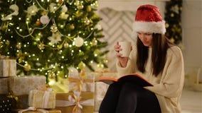 Jovem mulher bonita que veste Santa Hat Sitting em casa e que come a bebida quente ao ler um livro Morena bonita filme