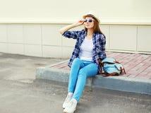 Jovem mulher bonita que veste um chapéu de palha do verão dos óculos de sol e uma camisa quadriculado com trouxa Imagem de Stock Royalty Free