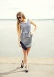 Jovem mulher bonita que veste um vestido listrado, óculos de sol e embreagem da bolsa foto de stock royalty free