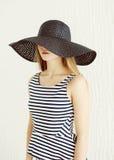 Jovem mulher bonita que veste um vestido listrado, chapéu de palha preto foto de stock