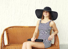Jovem mulher bonita que veste um vestido listrado, um chapéu de palha preto e uma embreagem da bolsa imagens de stock royalty free