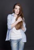 A jovem mulher bonita quer saber se precisa de cortar seu cabelo Fotos de Stock