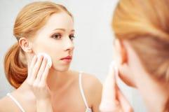 A jovem mulher bonita remove a composição com a pele da cara Fotos de Stock Royalty Free