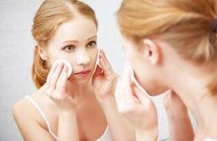 A jovem mulher bonita remove a composição com a pele da cara no mirro Imagem de Stock Royalty Free