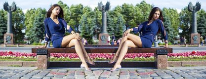 A jovem mulher bonita senta-se em um banco Fotografia de Stock