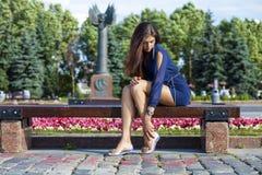 A jovem mulher bonita senta-se em um banco Fotos de Stock Royalty Free