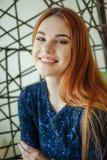 A jovem mulher bonita senta-se em uma cadeira do pendente na sala Imagem de Stock