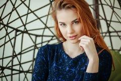 A jovem mulher bonita senta-se em uma cadeira do pendente na sala Imagem de Stock Royalty Free