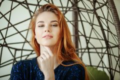 A jovem mulher bonita senta-se em uma cadeira do pendente na sala Imagens de Stock