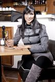 A jovem mulher bonita senta-se no coffeeshop. Imagens de Stock Royalty Free