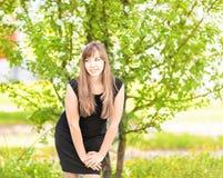 A jovem mulher bonita sobre a árvore branca da flor, salta fora retrato Fotos de Stock