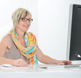 Jovem mulher bonita superior que trabalha no escritório com computador Foto de Stock