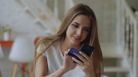 A jovem mulher bonita tem a operação bancária em linha e a compra usando o smartphone e o cartão de crédito em casa imagem de stock