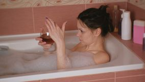 A jovem mulher bonita toma um banho com um vidro do uísque em sua mão Mergulha seu dedo no uísque e nos gostos filme