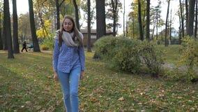 A jovem mulher bonita veste o lenço feito malha e o passeio no parque do outono Movimento video filme