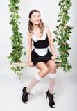 Jovem mulher bonita vestida como um empregada-empregado 'sexy' em um uniforme skimpy, levantando provocatively e balançando em um Foto de Stock Royalty Free