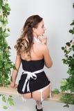 Jovem mulher bonita vestida como um empregada-empregado 'sexy' em um uniforme skimpy, levantando provocatively e balançando em um Foto de Stock