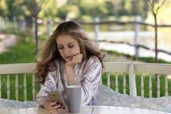 A jovem mulher bonita vestida no peignoir de seda está olhando-a Imagens de Stock Royalty Free