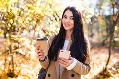 Jovem mulher bonita vestida no revestimento do outono fora, bebendo o caf?, usando o telefone celular foto de stock