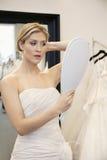 A jovem mulher bonita vestiu-se acima no vestido de casamento que olha o espelho disponivel Fotografia de Stock
