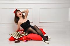 Jovem mulher bonito em um vestido preto e em meias senta-se em um coxim vermelho e prepara-se para a data Usa cosm?ticos e verniz imagens de stock