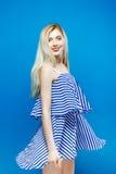 A jovem mulher bonito está levantando no estúdio Retrato do vestido listrado vestindo do verão do louro bonito no fundo azul Imagens de Stock Royalty Free