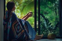 Jovem mulher bonito no café de assento e bebendo do poncho e que olha na parte externa da chuva fotos de stock
