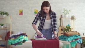 Jovem mulher bonito no ferro passando da lavanderia da camisa de manta em casa filme