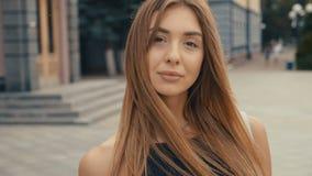 A jovem mulher bonito no olhar da rua na câmera, steadicam disparou Fim fêmea da cara bonita do verão da forma do retrato acima filme