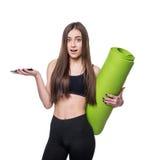 Jovem mulher bonito no sportswear com a esteira verde pronta para o exercício Sorriso e fala no telefone Isolado no fundo branco fotos de stock royalty free