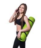 Jovem mulher bonito no sportswear com a esteira verde pronta para o exercício Sorriso e fala no telefone Isolado no fundo branco fotografia de stock