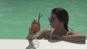A jovem mulher bonito nos óculos de sol está bebendo sua posição do cocktail na piscina Lazer da senhora só em um biquini filme